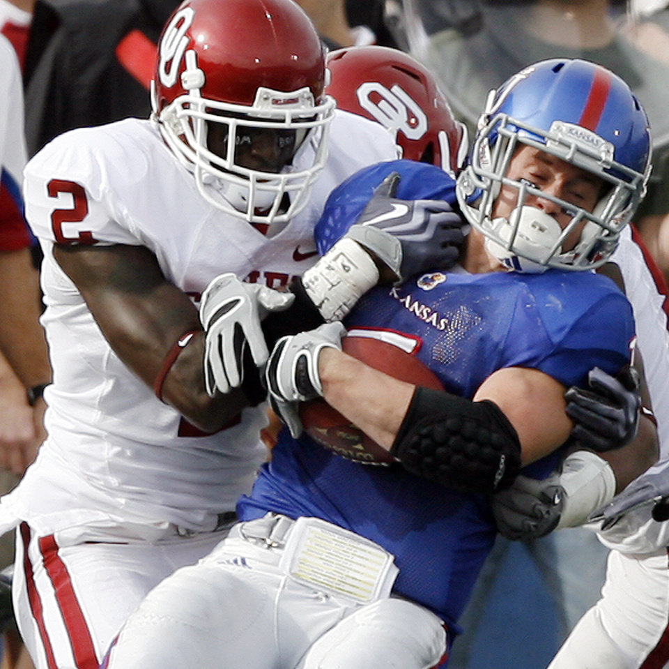 Photo - Oklahoma's Brian Jackson (2) brings down Kansas's Jake Sharp (1) during the first half of the college football game between the University of Oklahoma Sooners (OU) and the University of Kansas Jayhawks (KU) on Saturday, Oct. 24, 2009, in Lawrence, Kan. Photo by Chris Landsberger, The Oklahoman