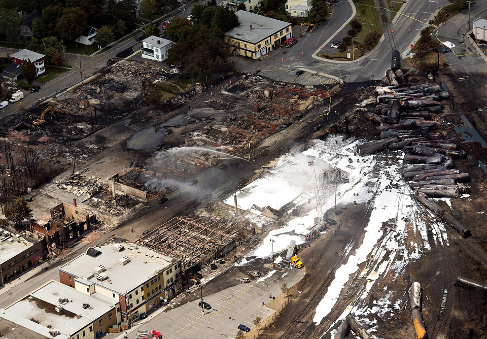 Photo - The downtown core lays in ruins as fire fighters continue to water smoldering rubble Sunday, July 7, 2013 in Lac Megantic, Quebec.  A runaway train derailed  Saturday igniting tanker cars carrying crude oil. (AP Photo/THE CANADIAN PRESS,Ryan Remiorz)
