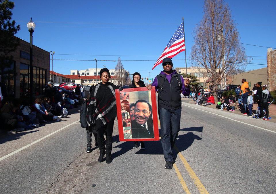 Photo - People walk holding a poster of Dr. King at the MLK Day Parade during celebration of Dr. Martin Luther King, Jr. holiday, Monday, January 20, 2019. [Photo by Doug Hoke/The Oklahoman]