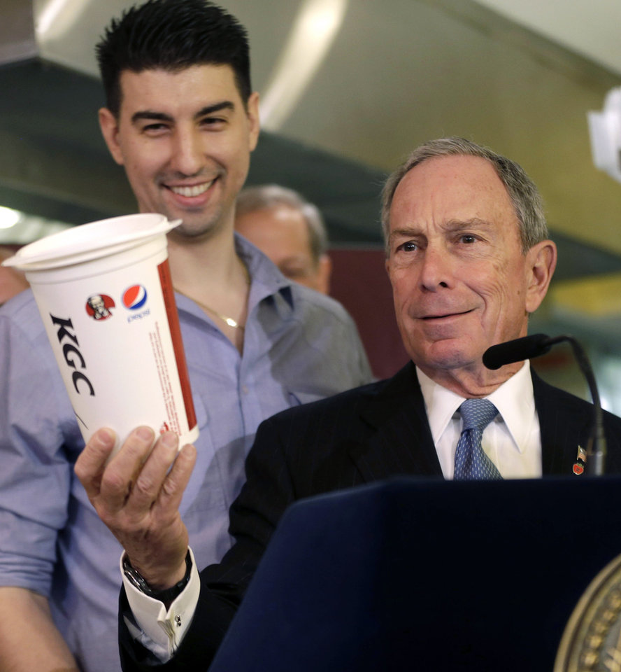 Photo - FILE - In this March 12, 2013 file photo, New York City Mayor Michael Bloomberg, right, looks at a 64oz cup, as Lucky's Cafe owner Greg Anagnostopoulos stands behind him, during a news conference at the cafe in New York. The New York Court of Appeals ruled Thursday, June 26, 2014 that the city's health department overstepped its bounds when it restricted the size of sodas. The court is siding with a lower court that overturned the 2012 ban.  (AP Photo/Seth Wenig, File)