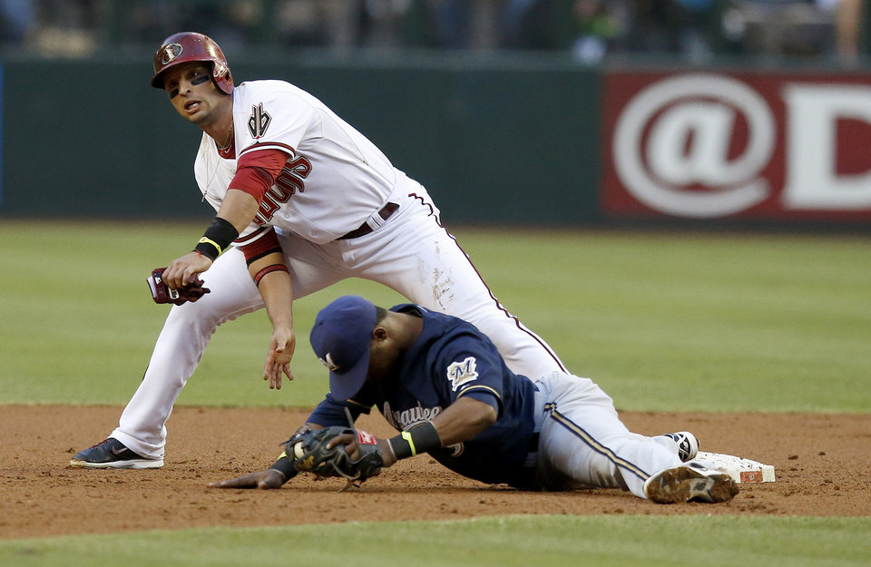 Photo - Arizona Diamondbacks' Martin Prado, left, collides with Milwaukee Brewers' Jean Segura after Prado was forced out at second base during the first inning of a baseball game on Tuesday, June 17, 2014, in Phoenix. (AP Photo/Ross D. Franklin)