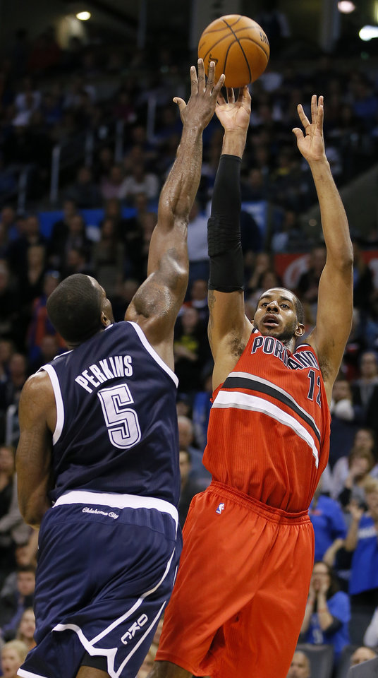 Photo - Portland's LaMarcus Aldridge (12) shoots over Oklahoma City's Kendrick Perkins (5) during an NBA basketball game between the Oklahoma City Thunder and the Portland Trail Blazers at Chesapeake Energy Arena in Oklahoma City, Tuesday, Dec. 31, 2013. Oklahoma City lost 98-94. Photo by Bryan Terry, The Oklahoman
