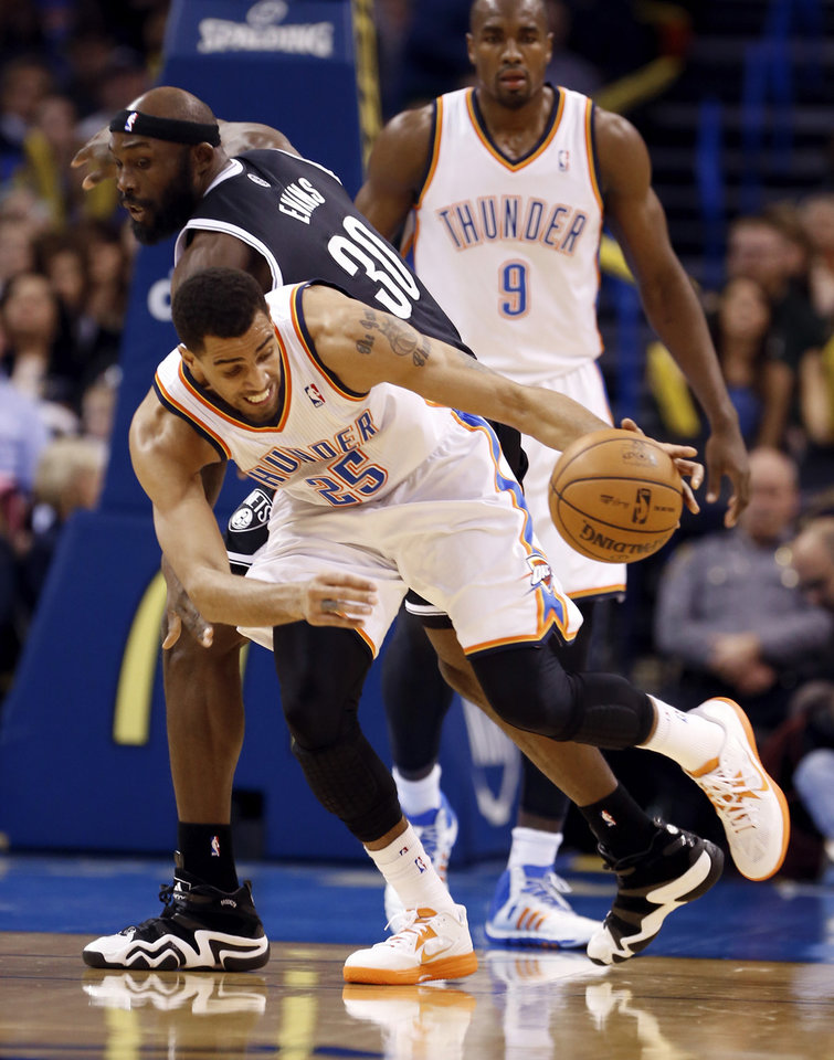 Photo - Thunder's Thabo Sefolosha steals the ball from Brooklyn's Reggie Evans (30) in the first half of an NBA basketball game where the Oklahoma City Thunder were defeated 95-93 by the Brooklyn Nets at the Chesapeake Energy Arena in Oklahoma City, on Thursday, Jan. 2, 2014. Photo by Steve Sisney The Oklahoman