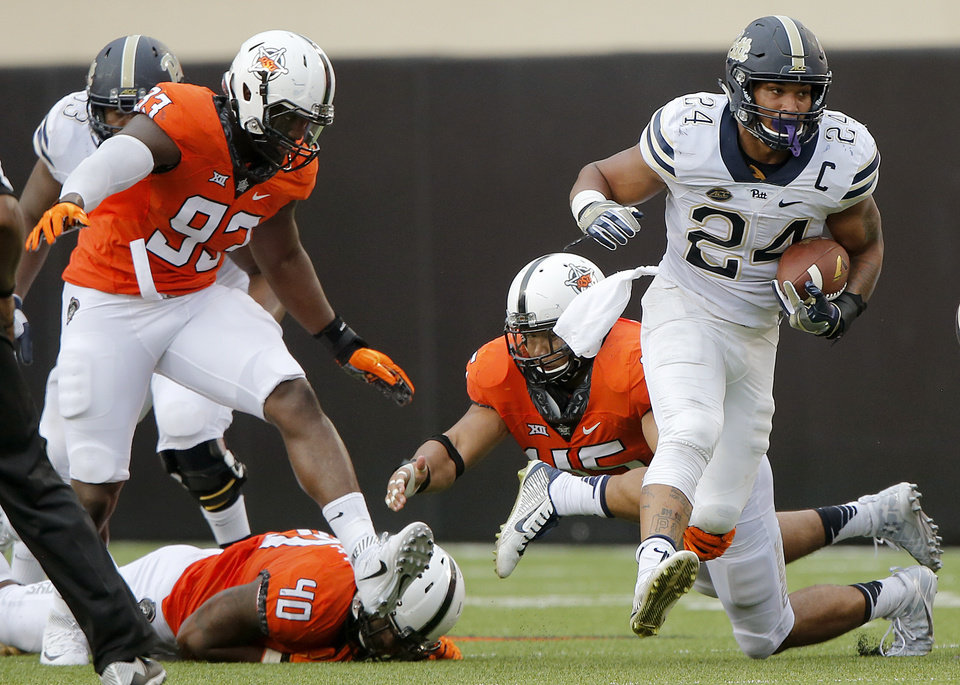 Photo - Pittsburgh's James Conner (24) runs past Oklahoma State's Jarrell Owens (93), Devante Averette (40) and Zach Smith (42) during a college football game between the Oklahoma State Cowboys (OSU) and the Pitt Panthers at Boone Pickens Stadium in Stillwater, Okla., Saturday, Sept. 17, 2016. Photo by Chris Landsberger, The Oklahoman
