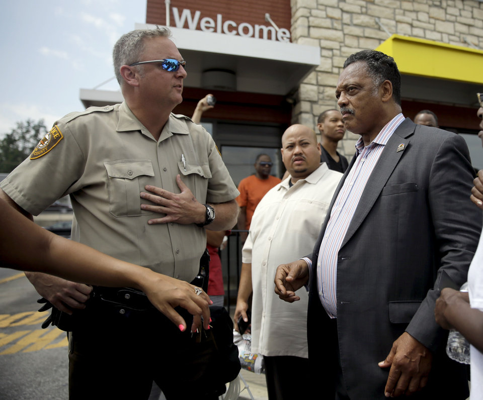 Photo - A member of the St. Louis County Police Department asks Rev. Jesse Jackson, right, to move along as they try to keep people from congregating, Monday, Aug. 18, 2014, in Ferguson, Mo. The Aug. 9 shooting of Michael Brown by police has touched off rancorous protests in Ferguson, a St. Louis suburb where police have used riot gear and tear gas. Gov. Jay Nixon ordered the National Guard to help restore order Monday while lifting a midnight-to-5 a.m. curfew that had been in place for two days. (AP Photo/Jeff Roberson)