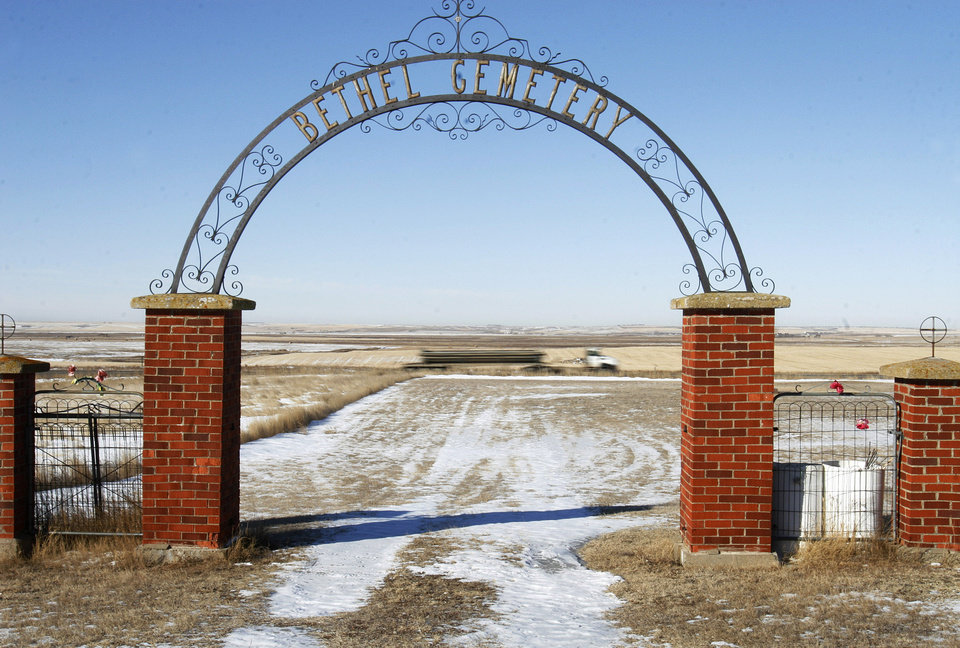 Photo - FILE - In this Feb. 27, 2014, file photo, an oil truck drives past a cemetery gate in Winner Township, N.D. The United States is still growing older, but the trend is reversing in the Great Plains, thanks to a liberal application of oil.  (AP Photo/Martha Irvine, File)