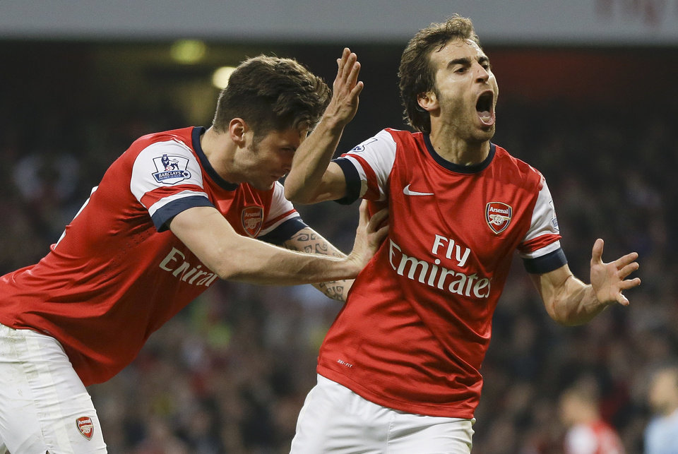 Photo - Arsenal's Mathieu Flamini, right, celebrates scoring a goal with Olivier Giroud during the English Premier League soccer match between Arsenal and Manchester City at the Emirates stadium in London, Saturday, March 29, 2014. (AP Photo/Kirsty Wigglesworth)