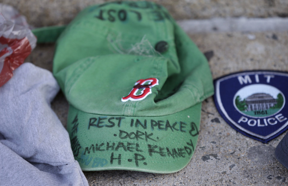Photo - A baseball cap with a written tribute to fallen Boston firefighter Michael Kennedy rests at a makeshift memorial in front of fire station Engine 33, Thursday, March 27, 2014, in Boston. Fire station Engine 33 was the station of fallen firefighters Kennedy and Lt. Edward Walsh and who lost their lives fighting a 9-alarm fire in a four-story brownstone in Boston's Back Bay neighborhood Wednesday, March 26, 2014. (AP Photo/Steven Senne)