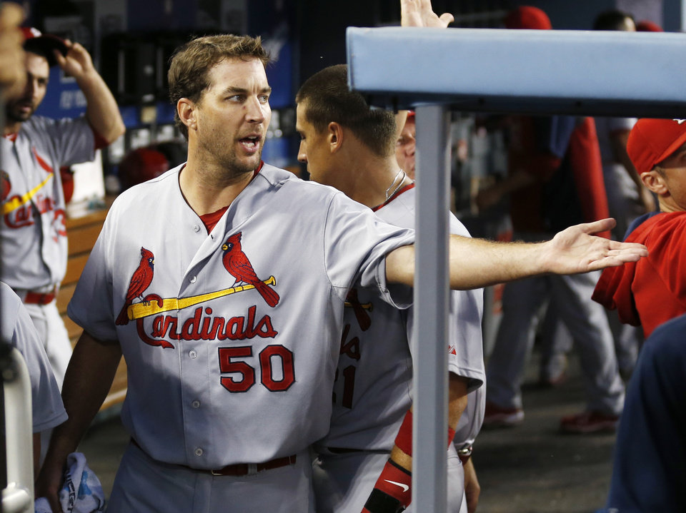 Photo - St. Louis Cardinals starting pitcher Adam Wainwright welcomes a teammate into the dugout after the fourth inning of a baseball game against the Los Angeles Dodgers, Thursday, June 26, 2014, in Los Angeles. (AP Photo/Danny Moloshok)