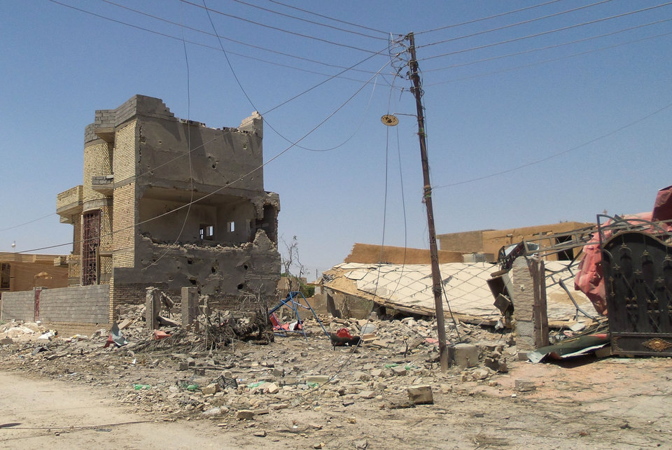 Photo - This photo taken on Tuesday, July 1, 2014, shows destroyed homes after clashes between fighters of the al-Qaida-inspired Islamic State of Iraq and the Levant and Iraqi security forces in Tikrit, 80 miles (130 kilometers) north of Baghdad, Iraq. The Islamic State of Iraq and the Levant announced this week that it has unilaterally established a caliphate in the areas under its control. It declared the group's leader, Abu Bakr al-Baghdadi, the head of its new self-styled state governed by Shariah law and demanded that all Muslims pledge allegiance to him. (AP Photo)