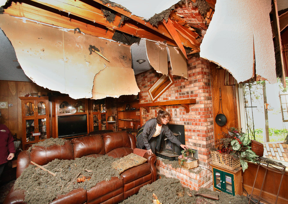 Photo - Tricia Hackbarth removes items Sunday morning from the family room of her parents' home as family and friends of Joseph and Mary Reneau began cleaning the mess created from Saturday's earthquakes.   A gaping hole in the ceiling was made when the chimney toppled onto the roof of the house.  An earthquake late Saturday night caused extensive damage to the two-story ranch style home of the  Reneaus.  near the community of Sparks in Lincoln County.  Contents inside their home were damaged earlier Saturday when a earthquake was struck the same area.  The Reneaus have lived in their house for 25 years. Photo by Jim Beckel, The Oklahoman  ORG XMIT: KOD