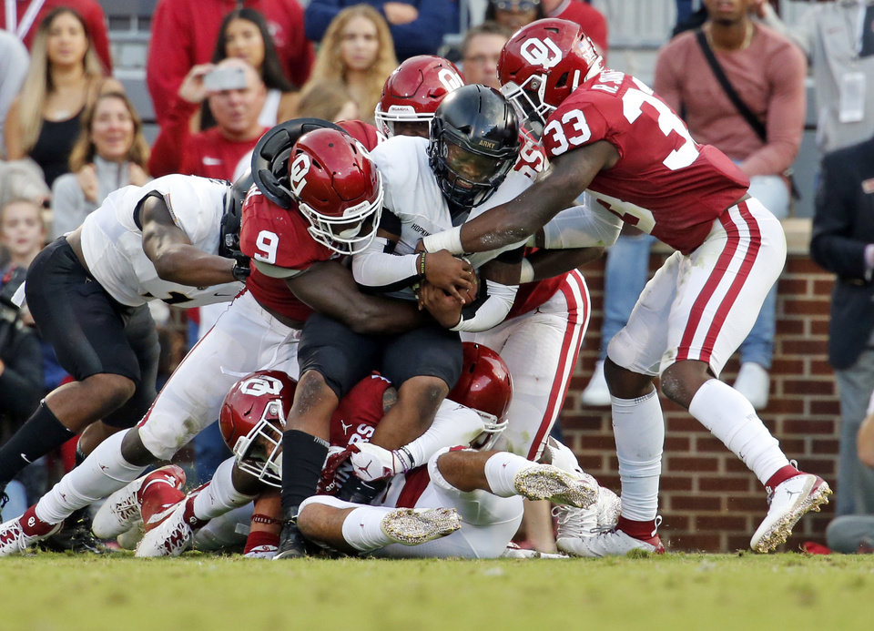 Photo - Oklahoma's Kenneth Murray (9) and Ryan Jones (33) bring down Army's Kelvin Hopkins Jr. (8) during a college football game between the University of Oklahoma Sooners (OU) and the Army Black Knights at Gaylord Family-Oklahoma Memorial Stadium in Norman, Okla., on Saturday, Sept. 22, 2018. Photo by Steve Sisney, The Oklahoman