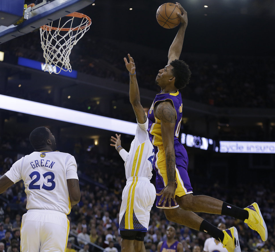 Photo - Los Angeles Lakers' Nick Young drives to score over Golden State Warriors' Kent Bazemore and Draymond Green (23) during the second half of an NBA basketball game, Saturday, Dec. 21, 2013, in Oakland, Calif. (AP Photo/Ben Margot)