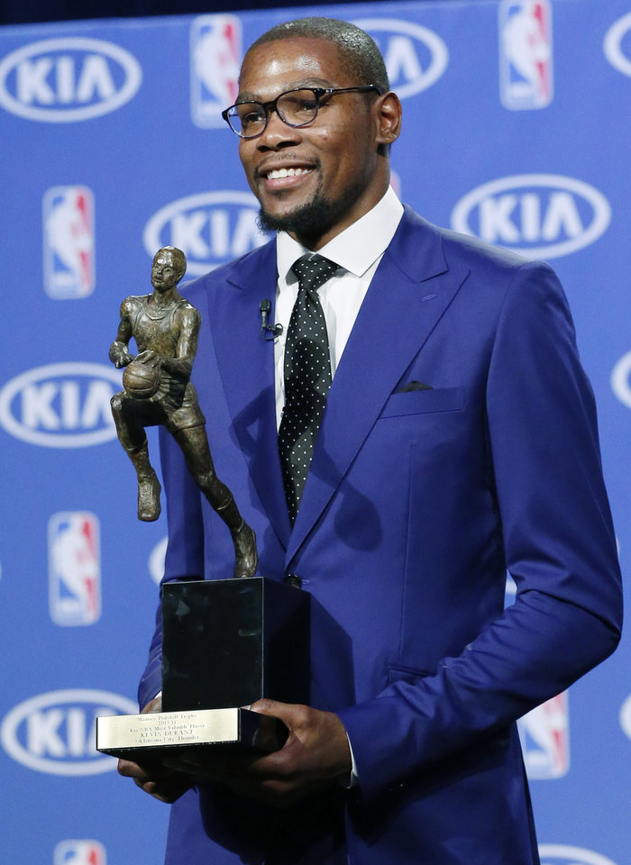 Photo - Oklahoma City Thunder's Kevin Durant poses with the MVP trophy following a news conference announcing  him as the winner of the 2013-14 Kia NBA Basketball Most Value Player Award in Oklahoma City, Tuesday, May 6, 2014. (AP Photo/Sue Ogrocki)