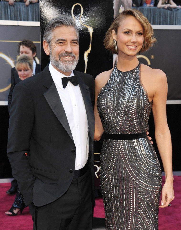 Photo - FILE - In this Feb. 24, 2013 file photo, actor George Clooney, left, and Stacy Keibler arrive at the Oscars at the Dolby Theatre in Los Angeles. Clooney, 52, Hollywood's most determined bachelor famous for a litany of fleeting loves, including Keibler, has taken himself off the romantic market and proposed to 36-year-old attorney, Amal Alamuddin. A spokesman for the Oscar-winning actor and producer did not respond to requests for comment Monday, April 28, 2014.  (Photo by John Shearer/Invision/AP, file)
