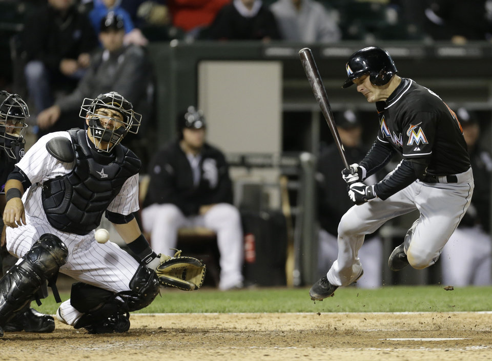 Photo - Miami Marlins' Nick Green, right, reacts after being hit by pitch as Chicago White Sox catcher Hector Gimenez also reacts during the 10th inning of a baseball game, Friday, May 24, 2013, in Chicago. (AP Photo/Nam Y. Huh)