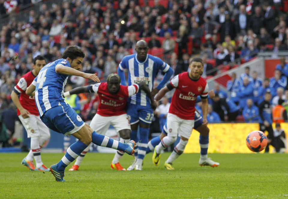 Photo - Wigan Athletic's Jordi Gomez scores a penalty against Arsenal during their English FA Cup semifinal soccer match at Wembley Stadium in London, Saturday, April 12, 2014. (AP Photo/Sang Tan)
