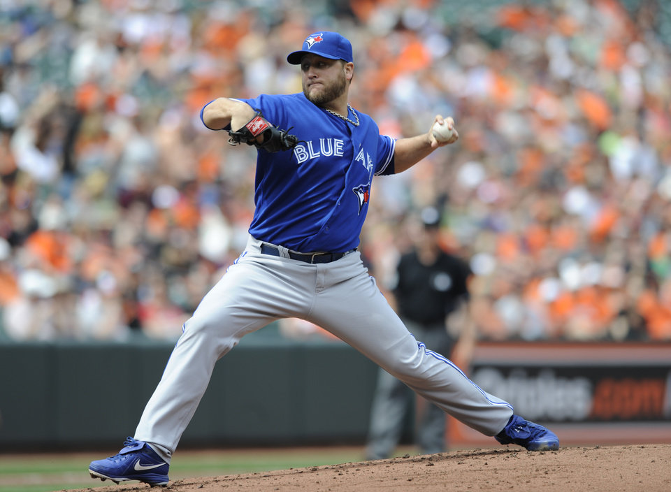 Photo - Toronto Blue Jays starting pitcher Mark Buehrle throws against the Baltimore Orioles in the first inning of a baseball game on Sunday, April 13, 2014, in Baltimore. (AP Photo/Gail Burton)