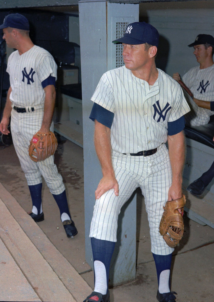 Photo - This is an undated photo showing baseball player Mickey Mantle, center, and other unidentified New York Yankees, in the dugout at Yankee Stadium in New York.  (AP Photo/File)