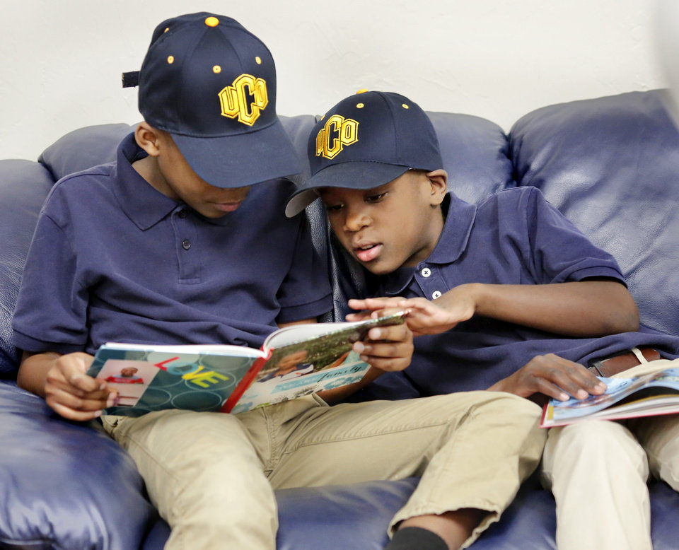 Photo - Two of Camden Cargill's younger brothers look at books while sharing  seats on a sofa in the room where their brother's signing ceremony was to begin soon. The boys are Creed, 9, and Cai, 8.  Cargill is one of the many local kids signing a National Letter of Intent on Wednesday, Feb. 7, 2018, but as much as his decision to sign with UCO is about football, it's also about family. He could've gone to a bigger school. He could've gone to an Ivy League program, even. But he's staying closer to home because of his five new brothers and sisters, all under the age of 10 and all adopted within the past year from Africa.   Photo by Jim Beckel, The Oklahoman