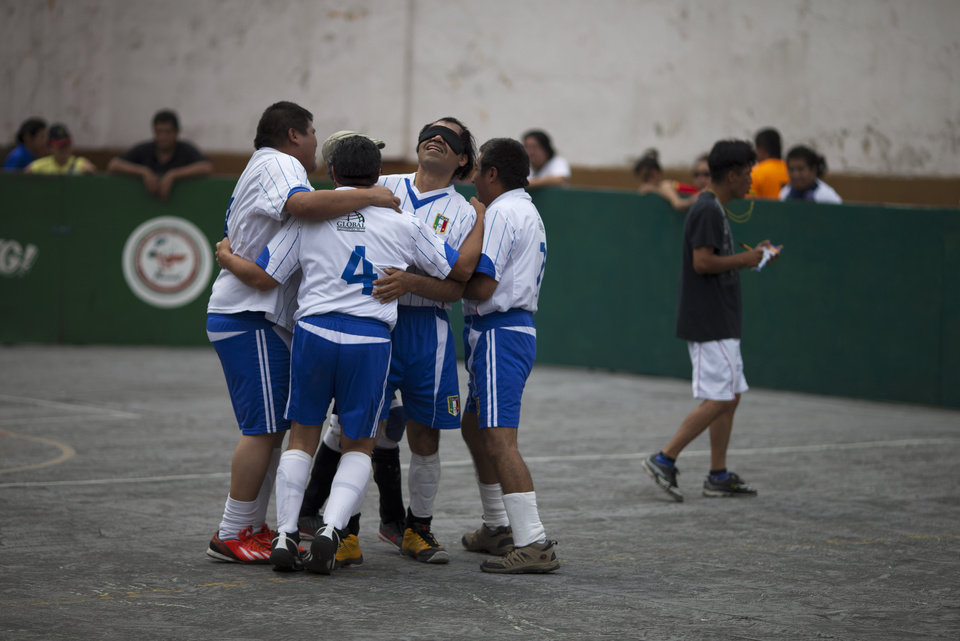 """Photo - In this Sunday, June 8, 2014 photo, Jose Luis Molina, center, celebrates with Italia teammates after they defeated the Leones Negros 6-5 in the 2014 final of the Ignacio Trigueros Soccer League for the Blind and Visually Impaired, in Mexico City. """"The concept of this league is just to spend time together, to unwind, to relieve stress, to relax,"""" says Molina. """"On the court, as in the farthest corners of the earth, there is rivalry; there are fights; there are spats. But socially, it's harmonious."""" (AP Photo/Rebecca Blackwell)"""