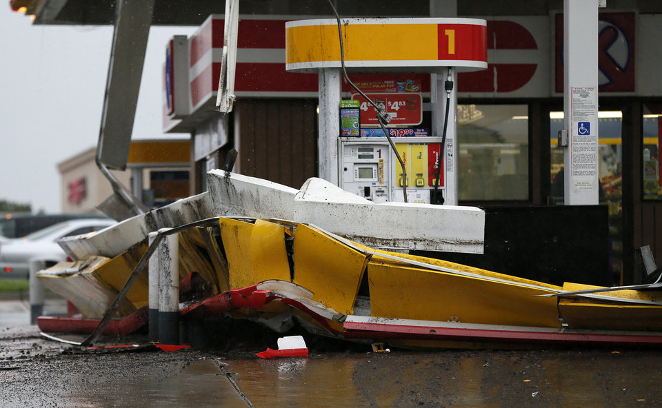Photo - Damage to the awning of a gas station on the southeast corner of NW 6rd and May during a thunder storm in Oklahoma City, Saturday, May 23, 2015. Photo by Nate Billings, The Oklahoman