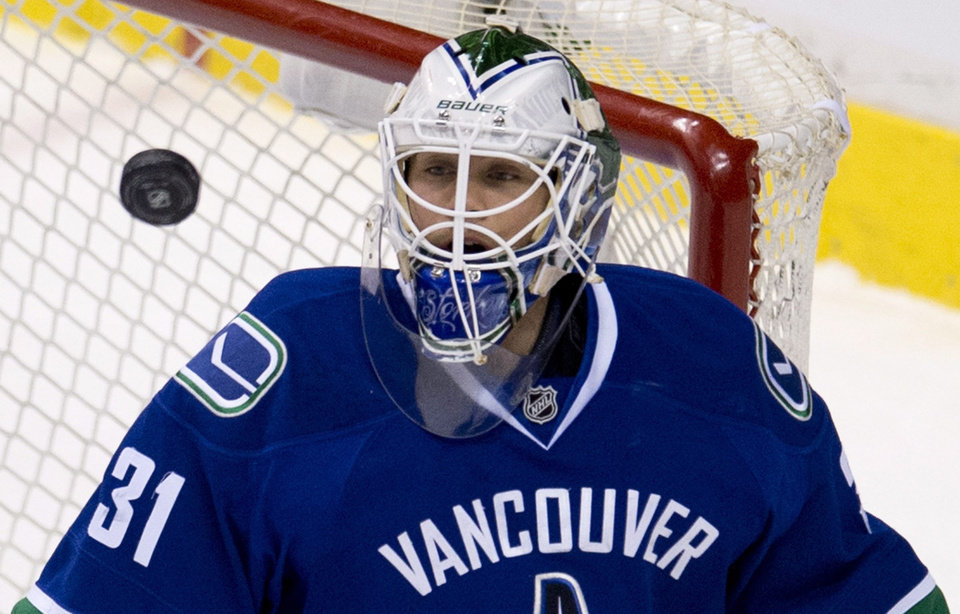 Photo - Vancouver Canucks goalie Eddie Lack (31) keeps his eye on the puck during the first period of NHL action against the Anaheim Ducks in Vancouver, British Columbia, on Monday, April 7, 2014. (AP Photo/The Canadian Press, Jonathan Hayward)