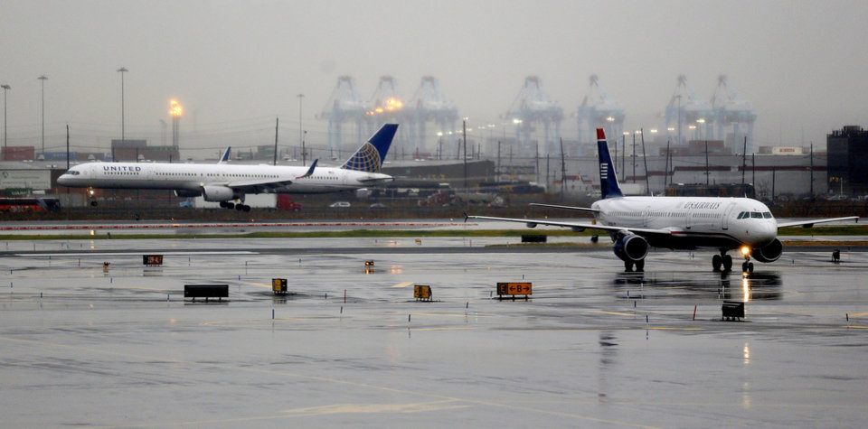 Photo - A plane, left, lands at Newark Liberty International Airport as another plane taxis, Thursday, Dec. 27, 2012 in Newark, N.J. An overnight storm caused minor delays at the airport. (AP Photo/Julio Cortez)