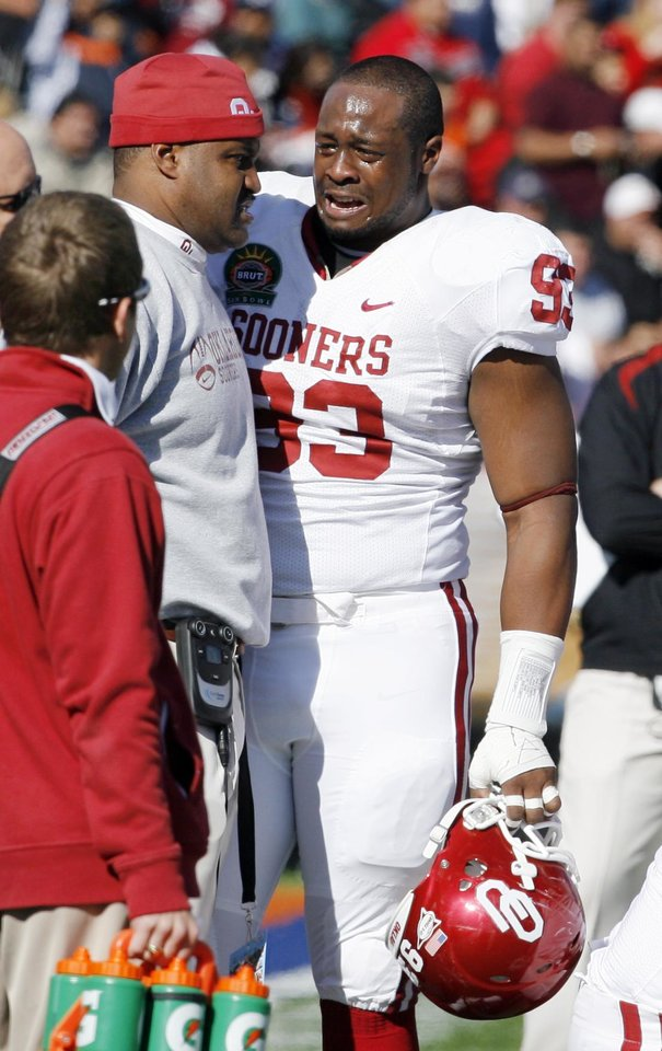 Photo - Gerald McCoy reacts as Ardrian Taylor (86) is injured during the first half of the Brut Sun Bowl college football game between the University of Oklahoma Sooners (OU) and the Stanford University Cardinal on Thursday, Dec. 31, 2009, in El Paso, Tex.   Photo by Steve Sisney, The Oklahoman