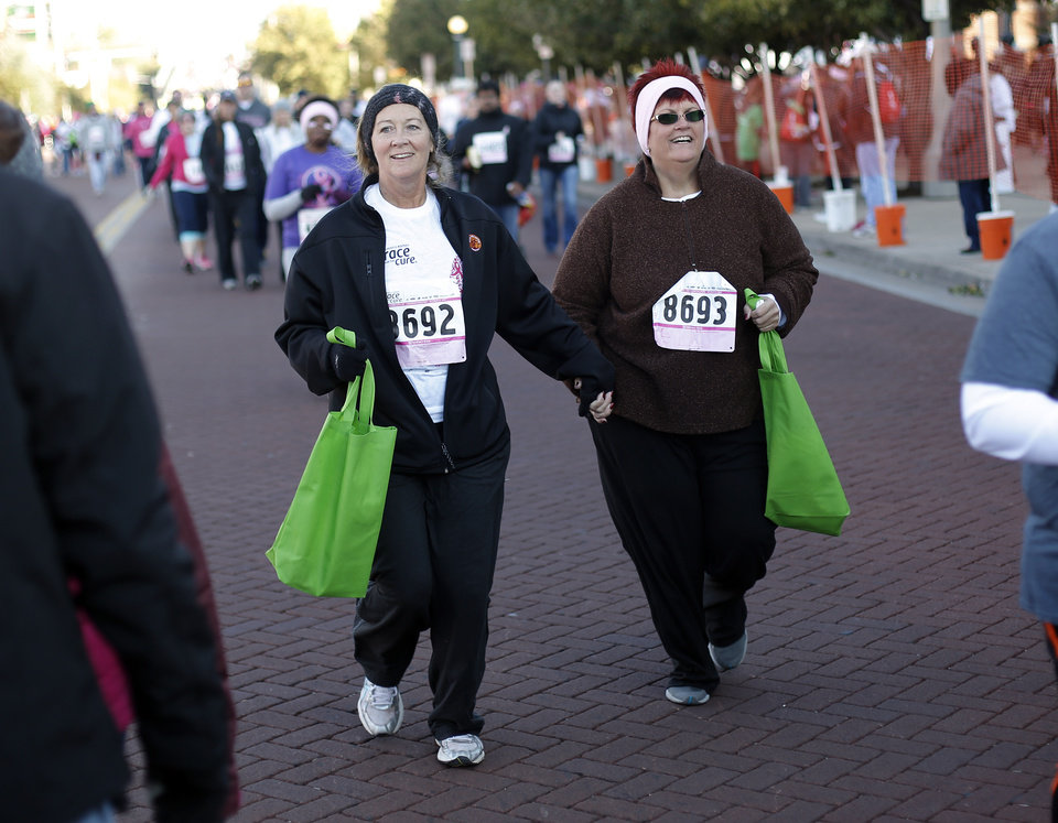Cathy Jordan, left, of Coyle, and Shelly McGregor, of Oklahoma City, cross the finish ling together during the 19th Annual Oklahoma City Race for the Cure at Chicasaw Bricktown Ballpark in Oklahoma City, Saturday, Oct. 27, 2012.  Photo by Garett Fisbeck, The Oklahoman