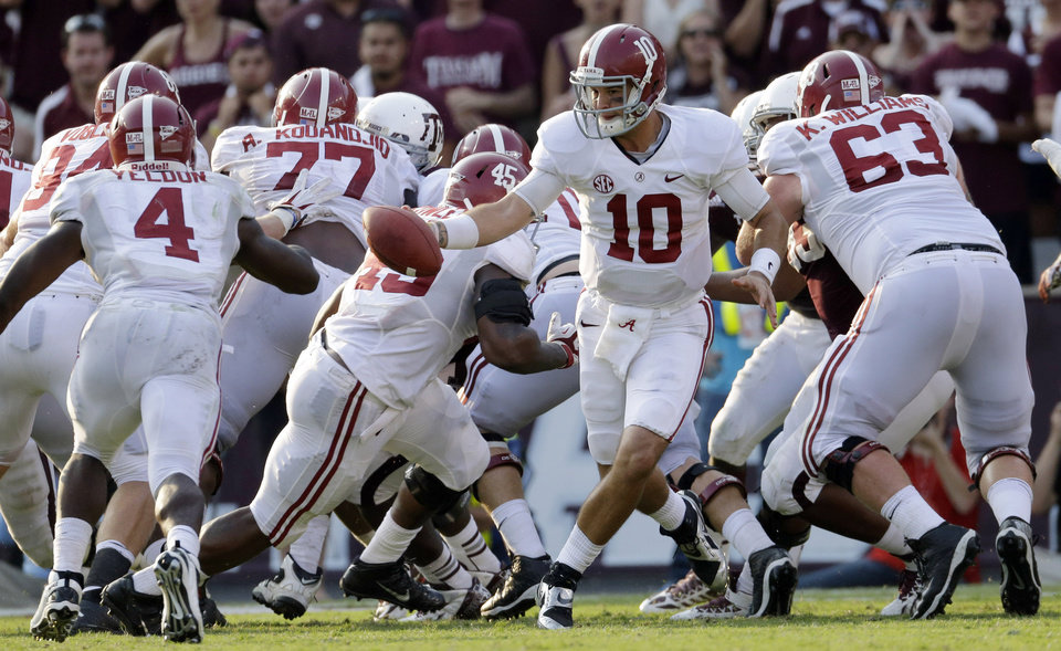 Photo - FILE - In this Sept. 14, 2013, file photo, Alabama quarterback AJ McCarron (10) hands the ball of to running back T.J. Yeldon during the fourth quarter of an NCAA college football game against Texas A&M in College Station, Texas.  While Yeldon has had nifty runs and decent numbers, the top-ranked Crimson Tide's ground game ranks last in the Southeastern Conference and the offense is only one spot higher in total yards. (AP Photo/David J. Phillip, File)