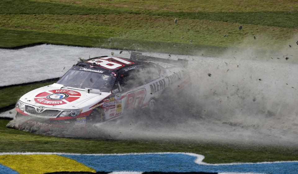 Driver Joe Nemechek slides through the grass after losing control of his car during the NASCAR Nationwide Series auto race Saturday, Feb. 23, 2013, at Daytona International Speedway in Daytona Beach, Fla. (AP Photo/Chris O'Meara)