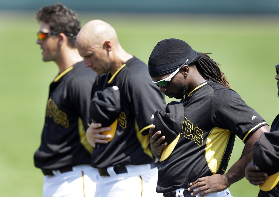 Photo - Pittsburgh Pirates, from left, shortstop Clint Barmes, first baseman Chris McGuiness and center fielder Andrew McCutchen stand during the national anthem before the first inning of a spring exhibition baseball game against the Baltimore Orioles in Bradenton, Fla., Monday, March 10, 2014. (AP Photo/Carlos Osorio)