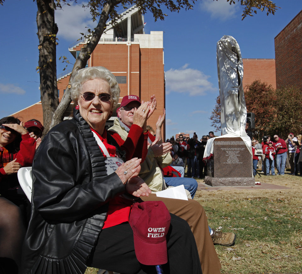 Photo - Dorothy Ann Owen Bryan, daughter of Benny Owen applauds as statues of 100 plus win head football coaches Benny Owen and Bud Wilkinson are unveiled before the college football game between the University of Oklahoma Sooners (OU) and the Texas Tech Red Raiders (TTU) across the street from the Gaylord Family Memorial Stadium on Saturday, Nov. 13, 2010, in Norman, Okla. 