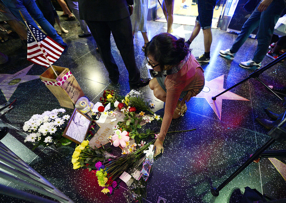 Photo - Flowers are placed in memory of actor/comedian Robin Williams on his Walk of Fame star in the Hollywood district of Los Angeles Monday, Aug. 11, 2014. Williams, the Academy Award winner and comic supernova whose explosions of pop culture riffs and impressions dazzled audiences for decades died Monday in an apparent suicide at his San Francisco Bay area home. He was 63. (AP Photo/Kevork Djansezian)