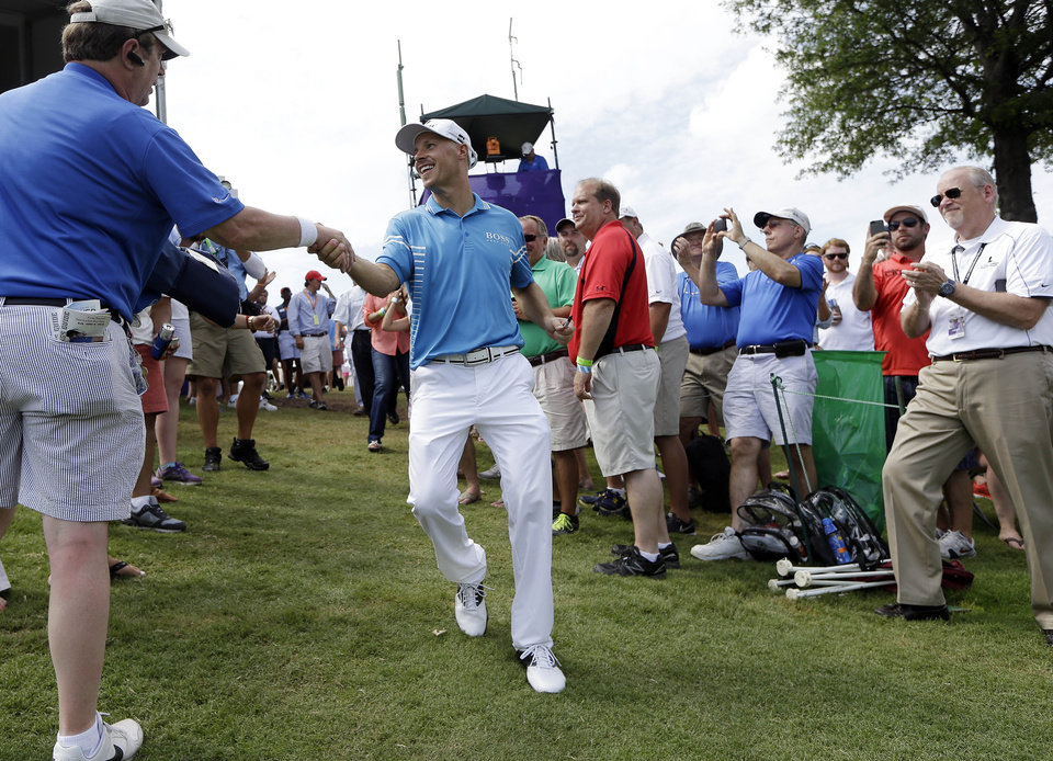Photo - Ben Crane, center, is congratulated as he walks to the 18th green for the award ceremony after winning the St. Jude Classic golf tournament Sunday, June 8, 2014, in Memphis, Tenn. Crane won the tournament with a score of 10-under 270.(AP Photo/Mark Humphrey)