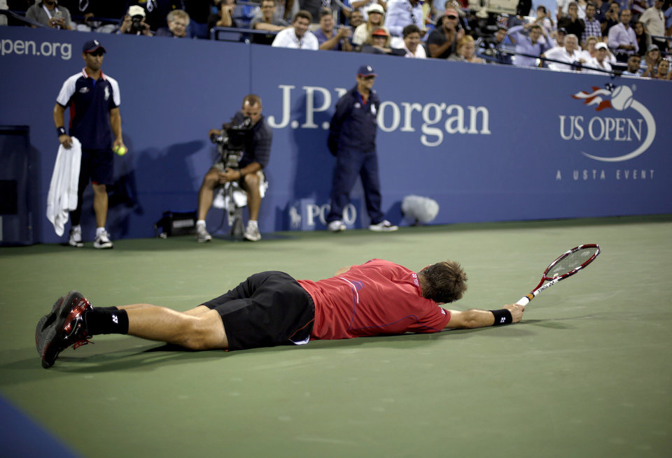 Photo - Stanislas Wawrinka, of Switzerland, lies on the court after slipping while reaching for a shot hit by Tomas Berdych, of the Czech Republic, during the fourth round of the U.S. Open tennis tournament, Tuesday, Sept. 3, 2013, in New York. (AP Photo/David Goldman)