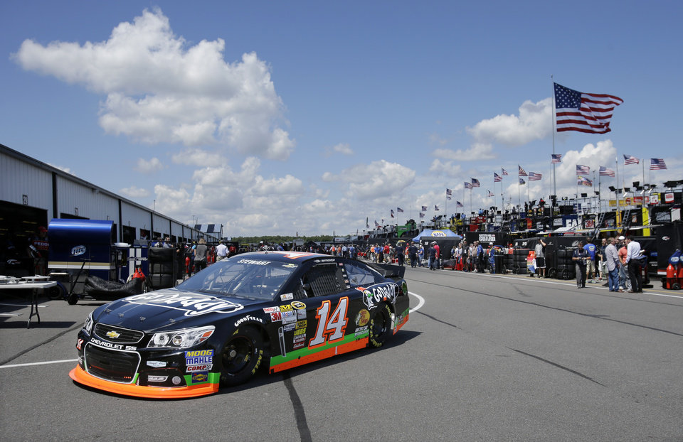 Photo - Tony Stewart drives in the garage area during practice Friday Aug. 2, 2013, for Sunday's NASCAR Sprint Cup Series auto race in Long Pond, Pa. (AP Photo/Mel Evans)