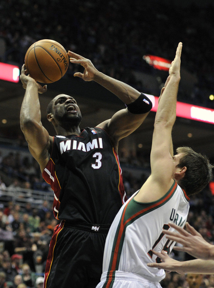 Miami Heat's Dwyane Wade (3) shoots the ball over Milwaukee Bucks' Beno Udrih during the first half of an NBA basketball game on Saturday, Dec. 29, 2012, in Milwaukee. (AP Photo/Jim Prisching)