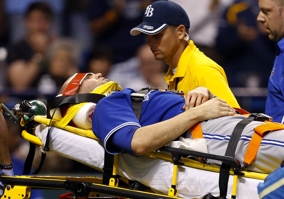 Photo - Toronto Blue Jays' J.A. Happ is attended to by medical personnel as he is taken off the field on a stretcher after being hit in the head by a line drive by Tampa Bay Rays' Desmond Jennings during the second inning of a baseball game Tuesday, May 7, 2013, in St. Petersburg, Fla. (AP Photo/Mike Carlson)