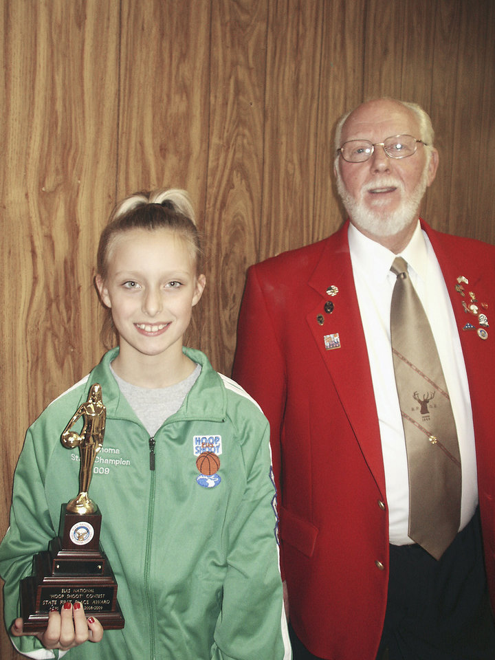 Photo - Cheyenne King of Midwest City stands next to Pete Clements, Hoop Shoot chairman.  PHOTO PROVIDED BY MIDWEST CITY ELKS LODGE
