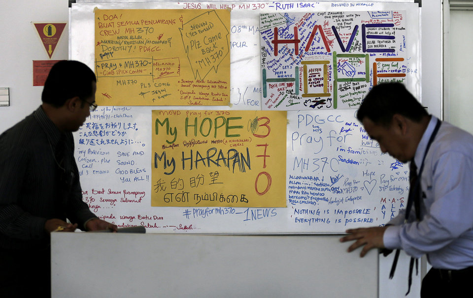 Photo - Airport staff move a white board plastered with messages of hope and encouragement to all involved with the missing Malaysia Airlines jet, MH370, at the Kuala Lumpur International Airport, Tuesday, March 11, 2014, in Sepang, Malaysia.  Authorities hunting for the missing Malaysia Airlines jetliner expanded their search on land and sea Tuesday, reflecting the difficulties in locating traces of the plane more than three days after it vanished.   (AP Photo/Wong Maye-E)