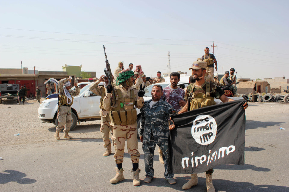 Photo - In this Monday, Sept. 1, 2014 photo, Shiite militiamen hold a flag of the Islamic State group they captured during an operation outside Amirli, some 105 miles (170 kilometers) north of Baghdad, Iraq. Aid began flowing into the small northern Shiite town in Iraq on Monday, a day after security forces backed by Iran-allied Shiite militias and U.S. airstrikes broke a two-month siege by insurgents in a rare victory by government forces. (AP Photo)