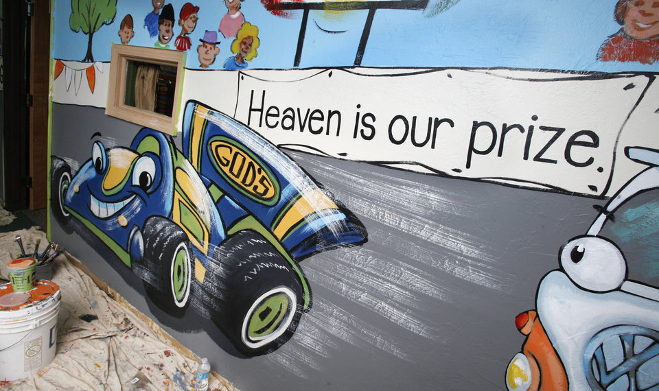 A mural featuring a race-track theme is painted by artists with Palmer Studios inside Oakcrest Church of Christ in Oklahoma City. PAUL B. SOUTHERLAND - PAUL B. SOUTHERLAND
