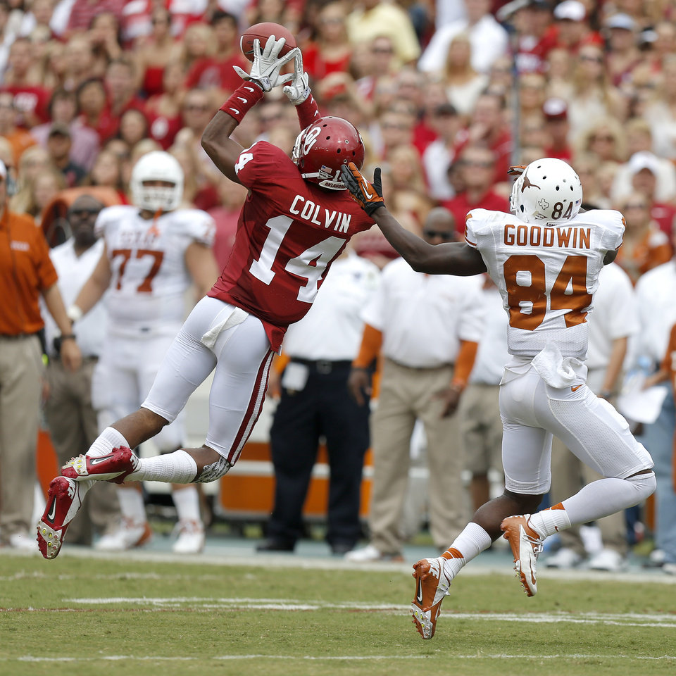 Photo - OU's Aaron Colvin (14) intercepts a pass intended for UT's Marquise Goodwin (84) during the Red River Rivalry college football game between the University of Oklahoma (OU) and the University of Texas (UT) at the Cotton Bowl in Dallas, Saturday, Oct. 13, 2012. Oklahoma won 63-21. Photo by Bryan Terry, The Oklahoman