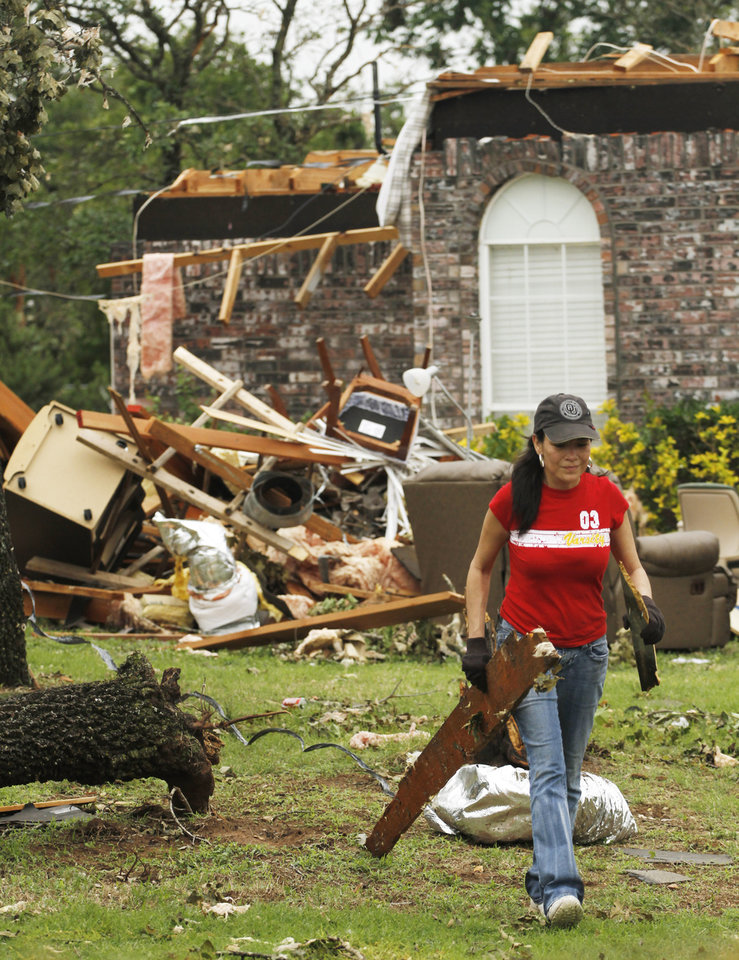 Catherine Godwin carries broken boards to the street in the Dripping Springs Estates Saturday, May 15, 2010. Saturday hundreds of volunteers went into areas that had been affected by last week's tornadoes to help clear debris. Photo by Doug Hoke, The Oklahoman.