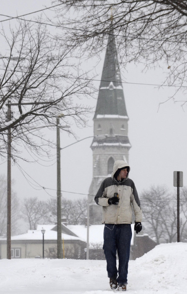 Photo - Gergory Cyr walks on Bradford Street as snow falls in Pittsfield, Mass., Wednesday Feb. 5, 2014. The storm is expected to drop a foot or more of snow on some areas of the state. (AP Photo/The Berkshire Eagle, Ben Garver)