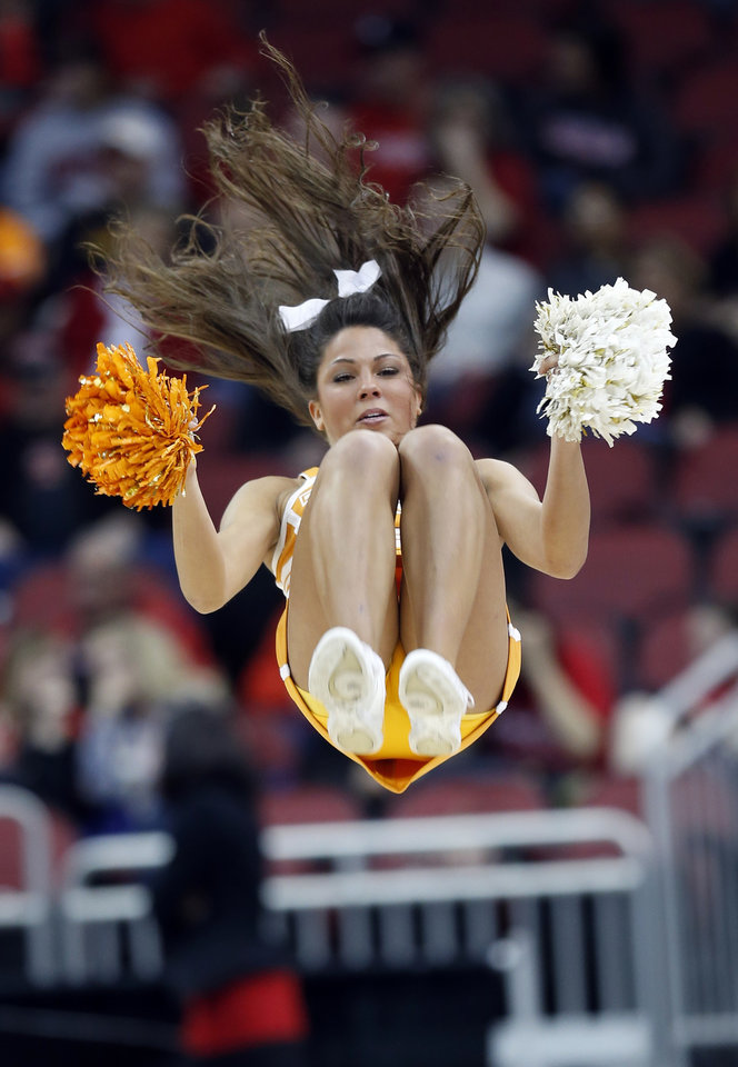 Photo - A Tennessee  cheerleader does a flip during a timeout during the first half of a regional semifinal game against Maryland at the NCAA college basketball tournament on Sunday, March 30, 2014, in Louisville, Ky. (AP Photo/John Bazemore)
