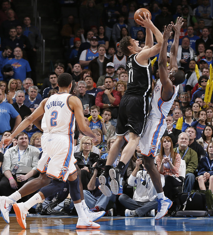 Photo - Oklahoma City's Serge Ibaka (9) tries to stop Brooklyn Nets' Brook Lopez (11) during the NBA basketball game between the Oklahoma City Thunder and the Brooklyn Nets at the Chesapeake Energy Arena on Wednesday, Jan. 2, 2013, in Oklahoma City, Okla. Photo by Chris Landsberger, The Oklahoman