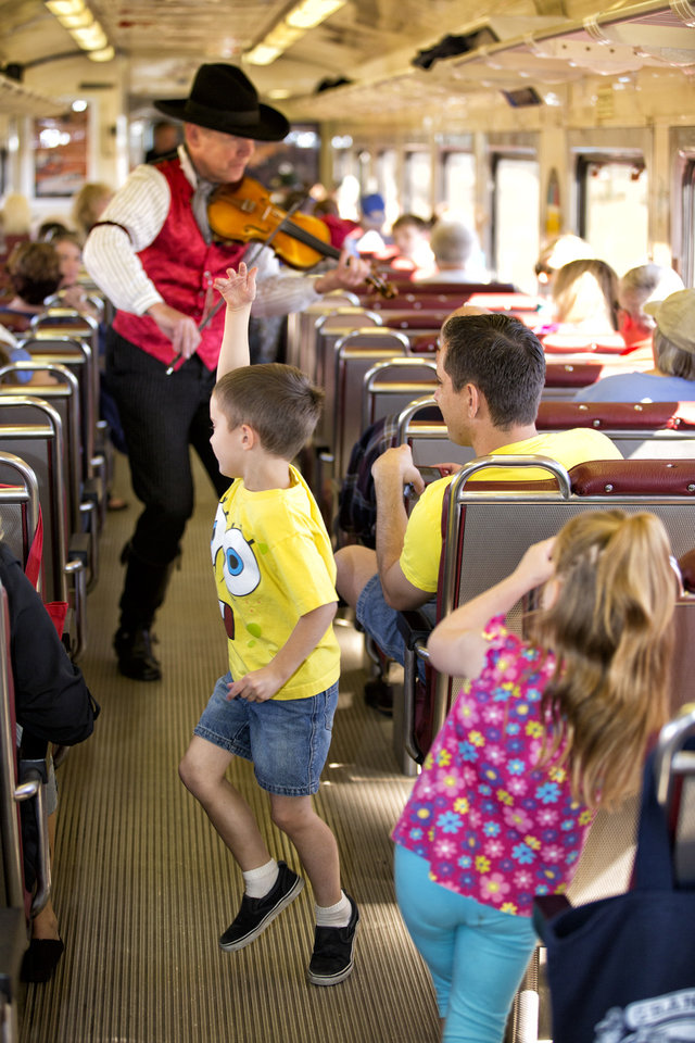 Photo - This photo provided by Grand Canyon Railway shows a performer playing violin onboard the railway train on its daily run between Williams, Arizona, and the Grand Canyon's South Rim. The railway has been running since 1901, carries 225,000 people a year, and offers history, sightseeing, scenery and entertainment. (AP Photo/Grand Canyon Railway)